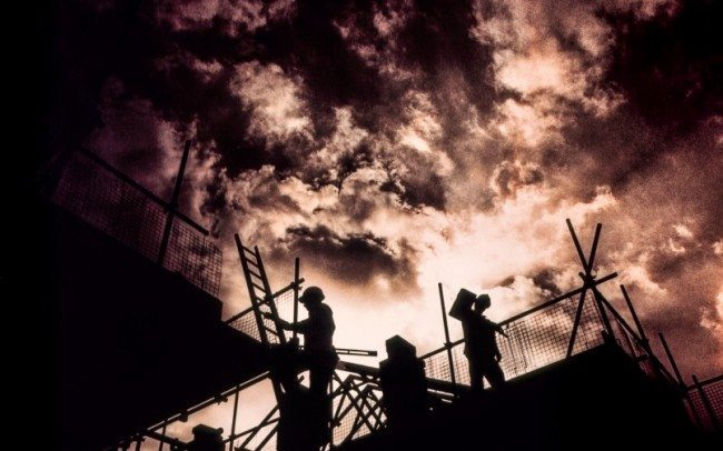 workers on building site silhouetted against red cloudy sky