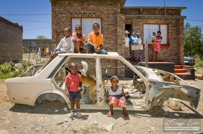 Boys playing in shell and roof of scrapped car