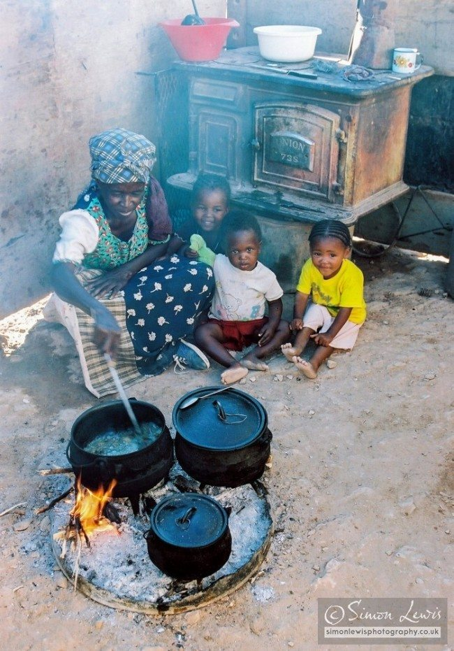 Mother cooking traditional cast iron pots in Gibeon