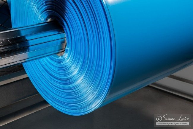 blue roll of plastic sheet being manufactured close-up