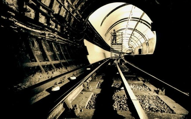 view along track inside london underground tunnel