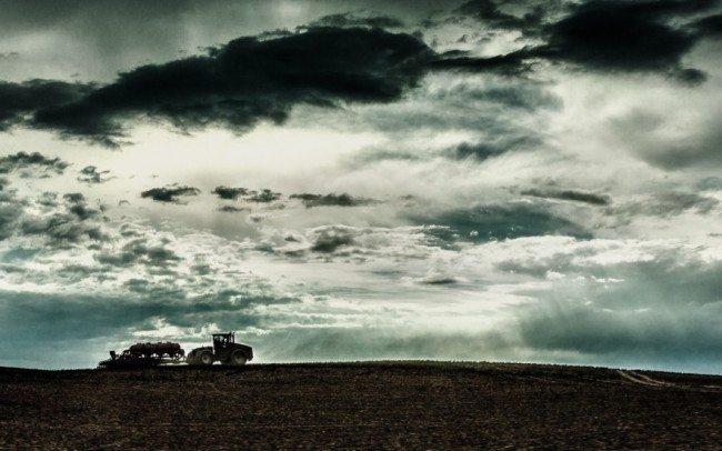 tractor ploughing fields silhouetted against stormy sky
