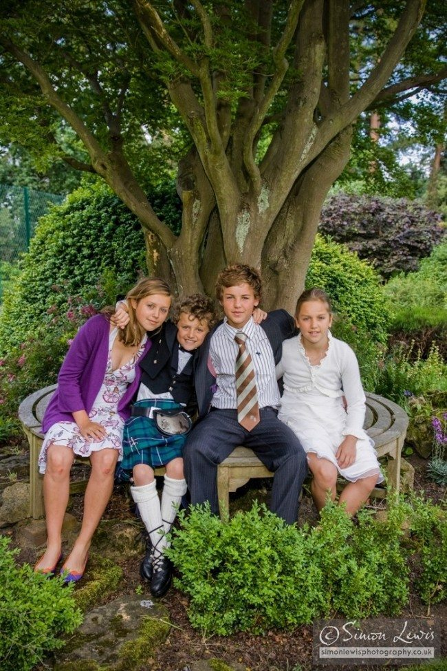 children group portrait in garden on bench arround tree