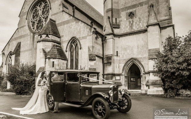 couple talking by car outside church sepia