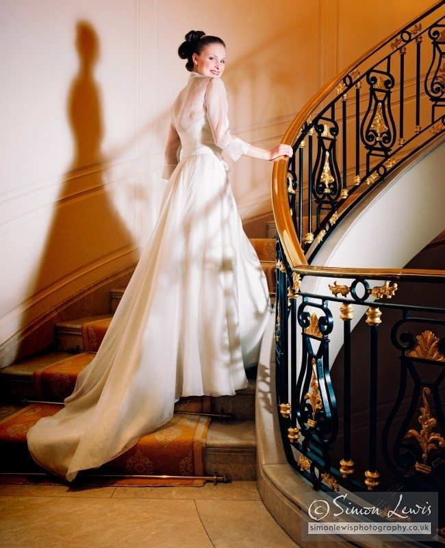 beautiful smiling bride in white dress on staircase