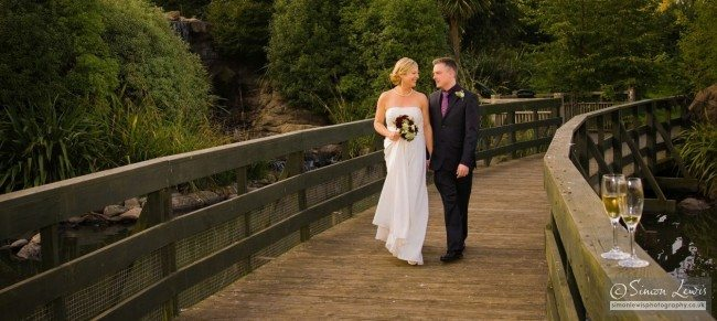 married couple talking and strolling across wooden bridge